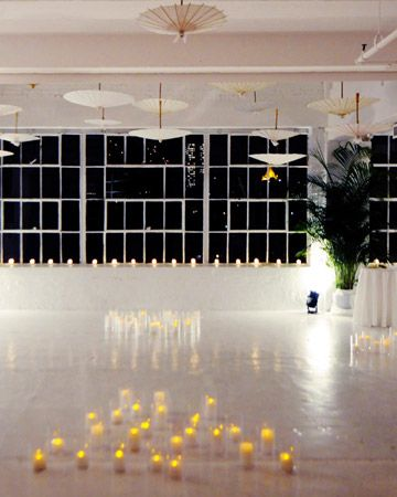 Real Wedding: Romney and Daron, New York City  The Dance Floor  Paper parasols hung from the ceiling above the glossy, white dance floor, faux candles scattered around the floor lit the space. Real candles lined the windowsills.  Next: The Cake