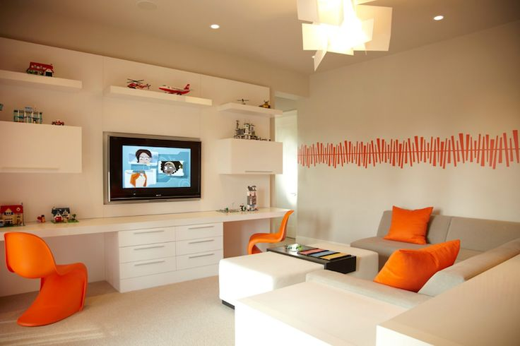 B + G Design     Modern playroom design with gray sectional sofa, orange pillows, white leather rectangular ottoman, orange panton chairs, chunky white desk, white file cabinets, white modern wall shelves, cabinets, chunky, white, floating shelves, orange wall stencils and modern light pendant.: Idea, Boys, Playroom, Boy Rooms, Desks, Family Room, Design, Kids Rooms