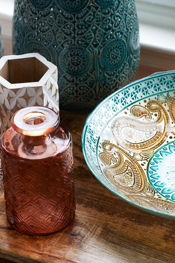 Embellished with ornate patterns, decorative ceramics, glassware and wooden accessories add a global note to the setting.