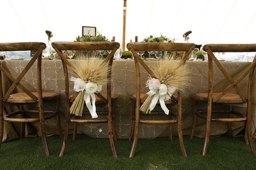 WEDDINGS: Bride and groom chairs decorated with wheat and bows, cute for