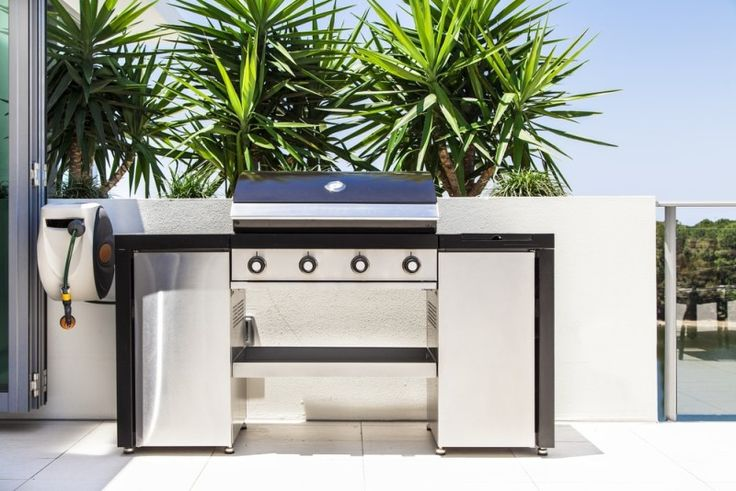 New outdoor stainless steel barbecue grill situated on a modern balcony