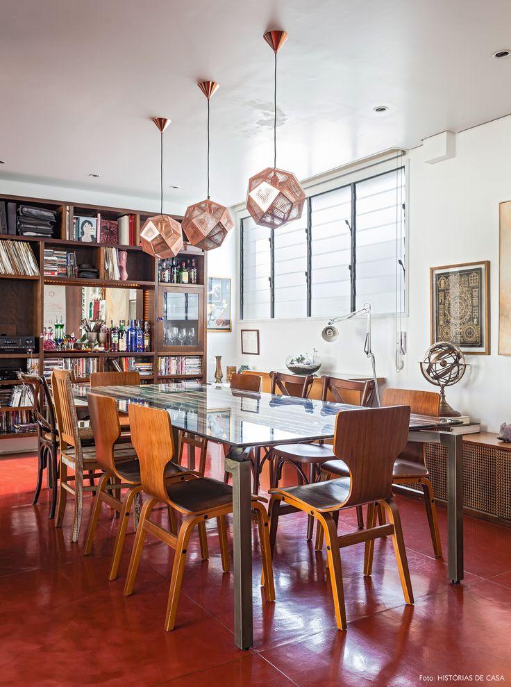 Sala de jantar tem mesa com tampo de pedra, cadeiras de madeira e luminárias Tom Dixon.