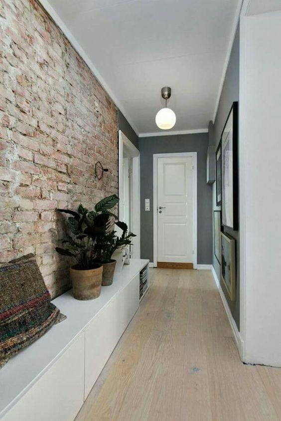 comment decorer un couloir avec mur en briques rouges brutes decoration couloir long et etroit parquet pvc imitation bois clair meuble blanc dis