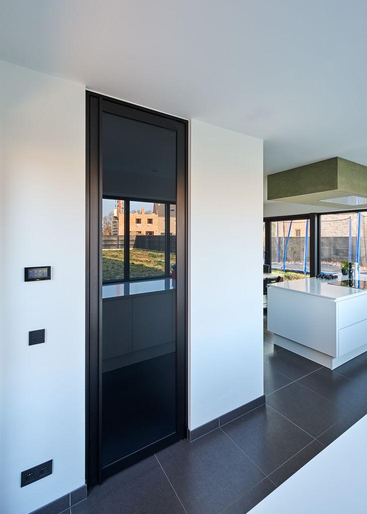 """Stalen deur concept met """"Grey"""" gezuurd glas tussen keuken en berging. De matte zijde zit aan de achterzijde en zorgt ervoor dat je niet door de deur kan kijken."""
