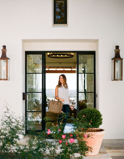 steel doors, sconces  and the symmetry between the front and back doors --- Austin home of Camille Styles