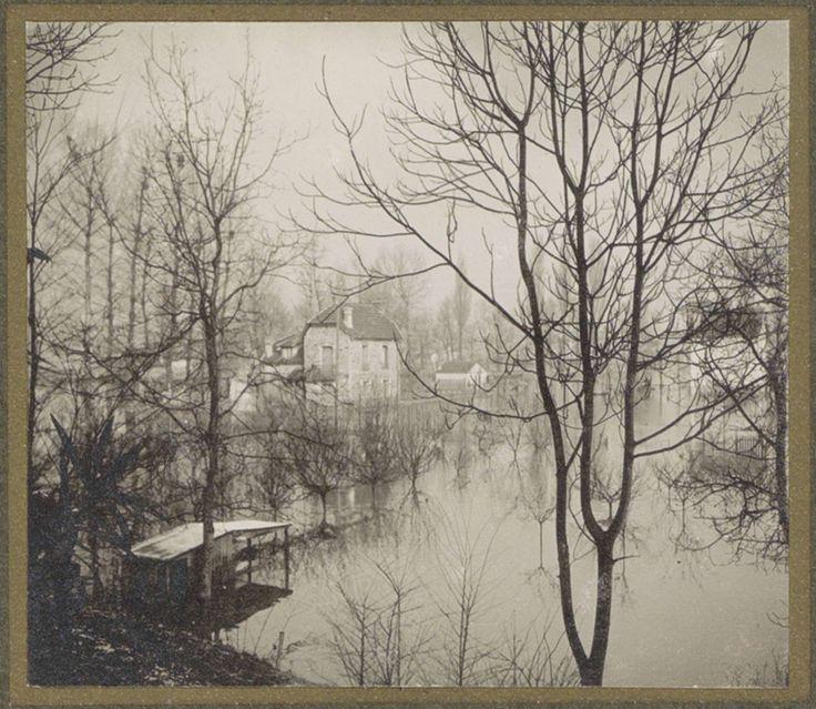 G. Dangereux | Huis in ondergelopen buitenwijk van Parijs gezien door kale bomen, G. Dangereux, 1910 | Onderdeel van fotoalbum overstroming Parijs en voorsteden 1910.