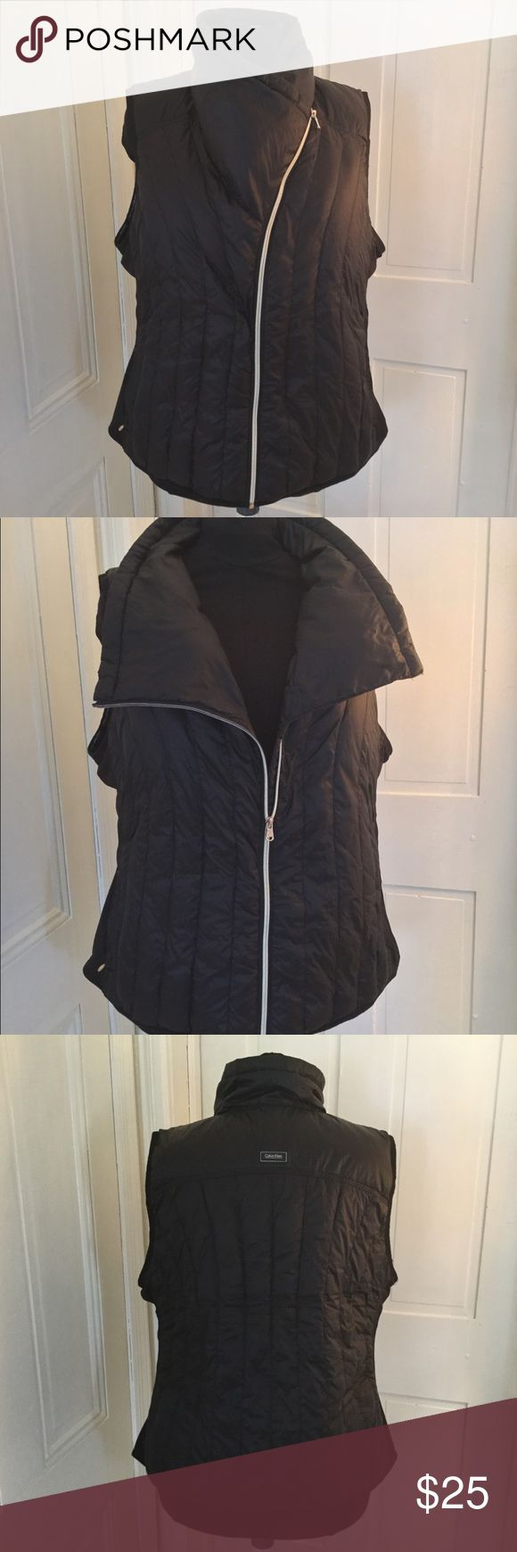 Calvin Klein Plus Size Puffer Vest Beautiful, barely used, black down vest with high funnel neck when fully zipped. Shell and Lining are 100% nylon. Fill is 90% down and 10% feathers. Sides have polyester and spandex elastic insets. Machine washable. Has zip security pockets (two), and headphone access gussets. Calvin Klein Jackets & Coats Puffers