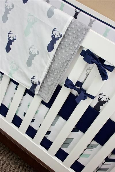 We are so in love with this deer crib bedding for your forest themed nursery! How adorable are those mint, navy and gray buck heads and feather arrows??