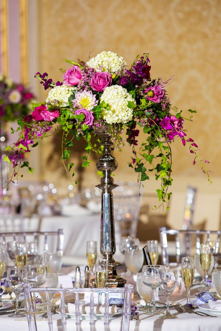 tall vase of white, purple and green flowers for a wedding centerpiece