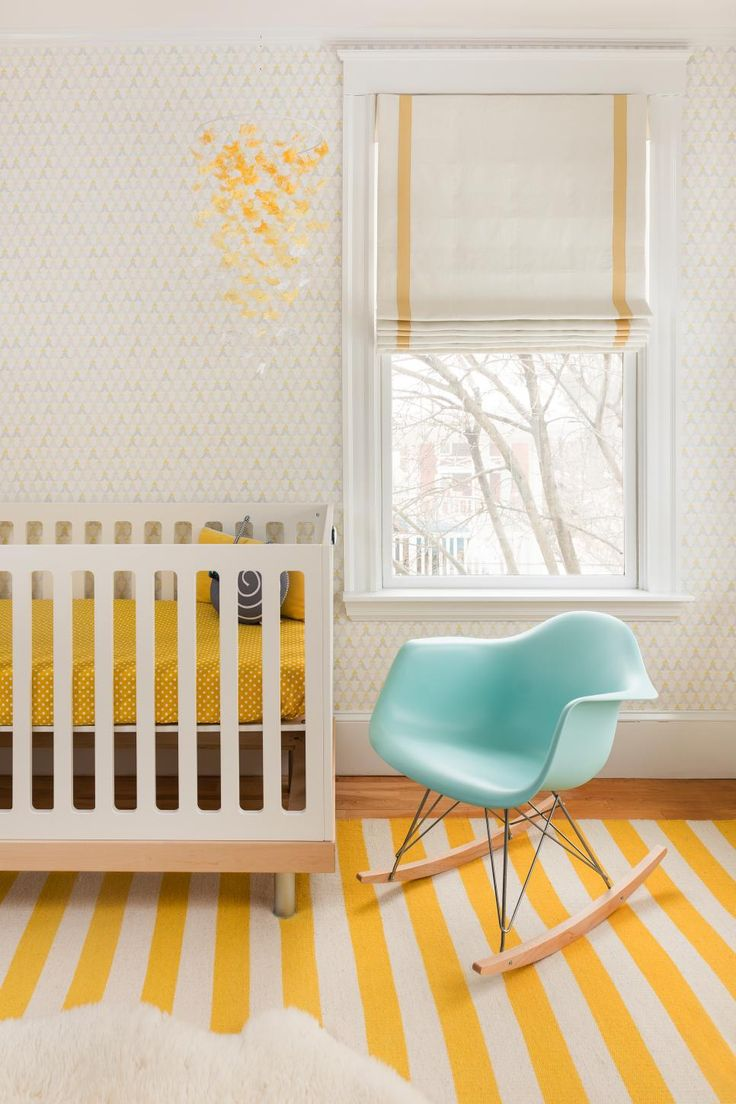 This white midcentury modern nursery features a white crib, white Roman shade, blue Eames rocking chair, and a yellow striped rug.