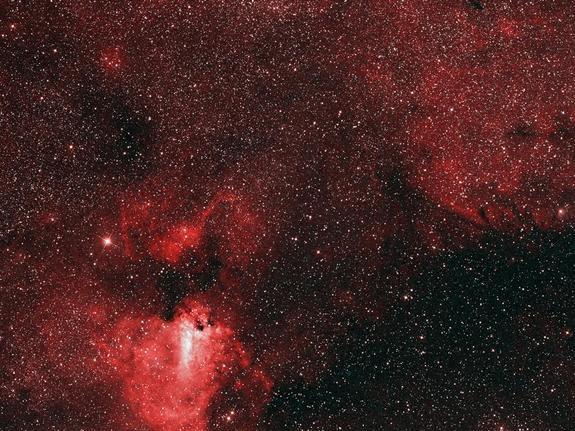 Este ponto de vista da luz visível do céu destaca a nebulosa brilhante M17, bem como o gás brilhante à sua esquerda. Enquanto jovens, estrelas quentes iluminam essas regiões, a grande faixa escura para a direita é uma extensa região de formação de estrelas, que só pode ser vista fora do espectro visível.