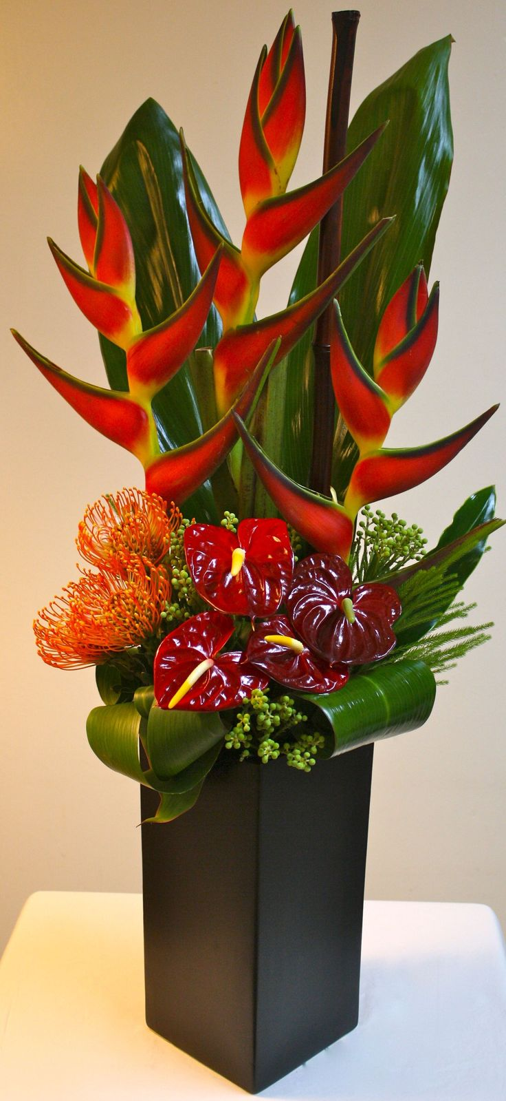 Jordan: A tropical mix of Orange Birds of Paradise, Orange Pin Cushions, Red Anthurium complimented with Green Tropical Leaves in a tall black ceramic vase. #Arreglosflorales