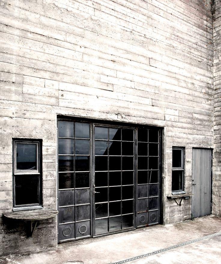 Industrial metal windows and door set into a vast concrete wall | warehouse…