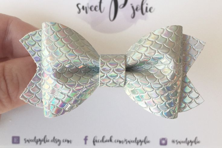 This is our Silver Iridescent Mermaid Scale Faux Leather Hair Bow. The hair bow is made out of high quality faux leather fabric. You choose if youd like the bow as either a hair clip or a headband! - If choosing a HAIR CLIP, your bow will come on a double prong alligator clip. You choose
