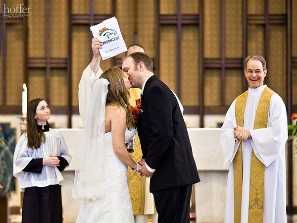 "These diehard Broncos fans added a fun twist to ""I now pronounce you husband and wife..."" by having the priest hold up a cheeky sign.Photo Credit: Hoffer Photography"