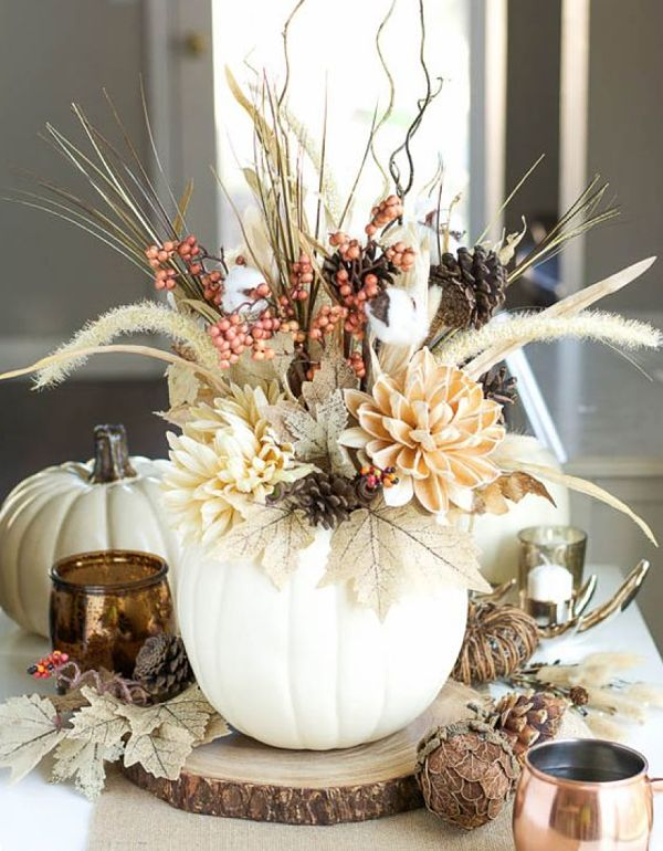 Fall Wedding Centerpiece: If you are celebrating your wedding in the fall, you may consider an autumn-themed centerpiece like this one. Another relatively simple DIY project, these faux flowers situated in a faux pumpkin are absolutely gorgeous. The details and the different textures make this centerpiece pop.
