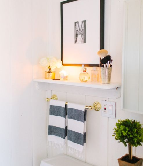 Alaina Veronica Kaczmarski Home - Bathroom features above the toilet shelf filled with fragrances paired with black and white photo frame din black gallery frame. below bathroom shelf is polished brass towel bar and West Elm Hammam Stripe Hand Towels.