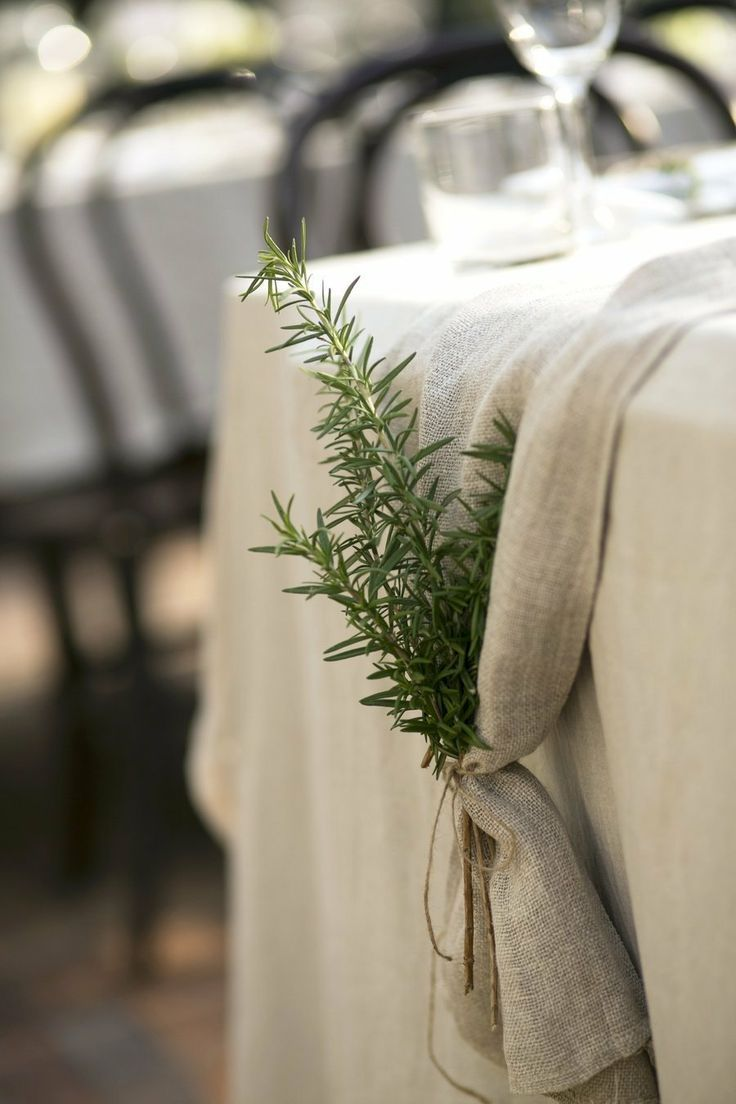 Rosemary sprigs in tied table runner over the edge of the table. Use fern and florals instead.