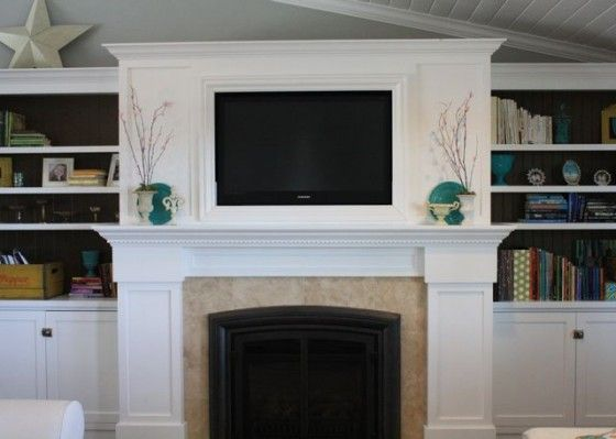 Love the tv into the mantle and the bookcases on either ...