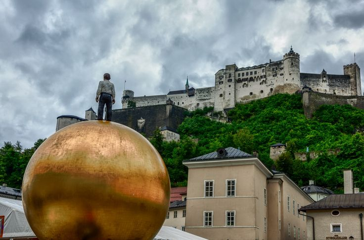 A brooding sky and a modern architectural element provides a dramatic view of Hohensalzburg Fortress in Salzburg, Austria.
