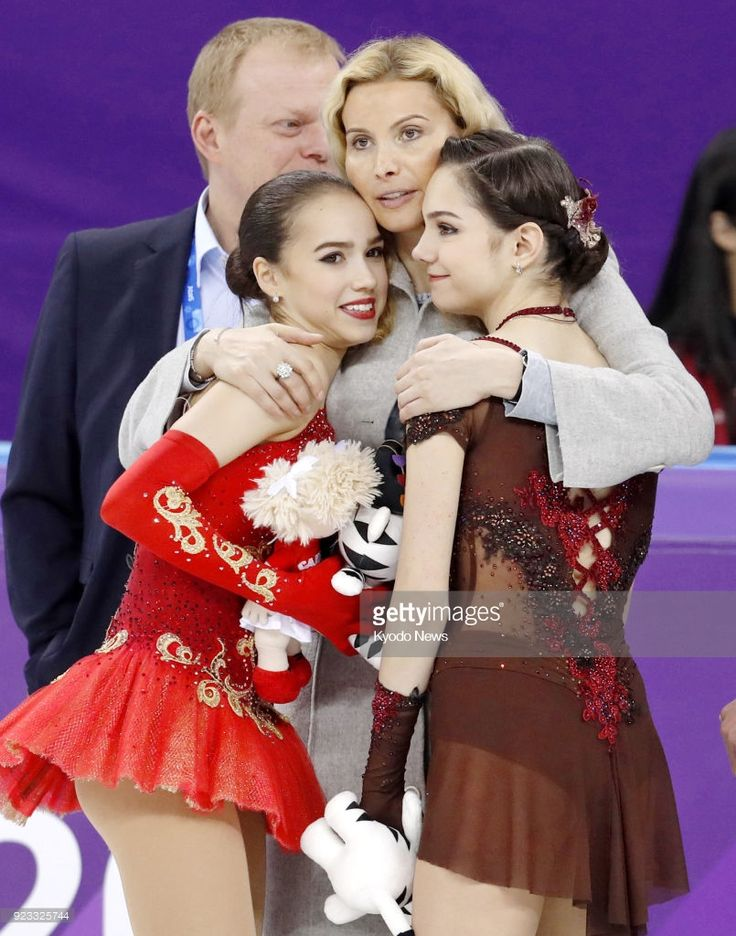 Olympic Athletes from Russia Alina Zagitova (L) and Evgenia Medvedeva (R) are hugged by their coach Eteri Tutberidze after winning gold and silver, respectively, in the women's figure skating at the Pyeongchang Winter Olympics in Gangneung, South Korea, on Feb. 23, 2018.  ==Kyodo