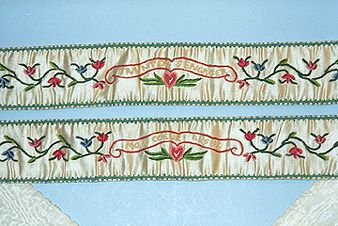 Ivory satin and silk garters to tie up Milady's stockings! The embroidered part of the garter is ten inches by 1 inch. Each garter has a different saying embroidered in French upon it. The embroidery is done on satin while the ties are of ivory silk.