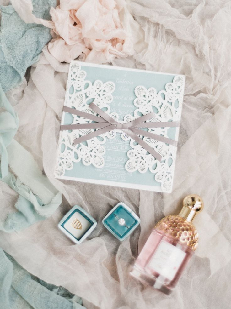 Beautiful wedding photography ideas - wedding invitation engagement ring and perfume on tulle and raw silk  Photography by We Are Origami Photo