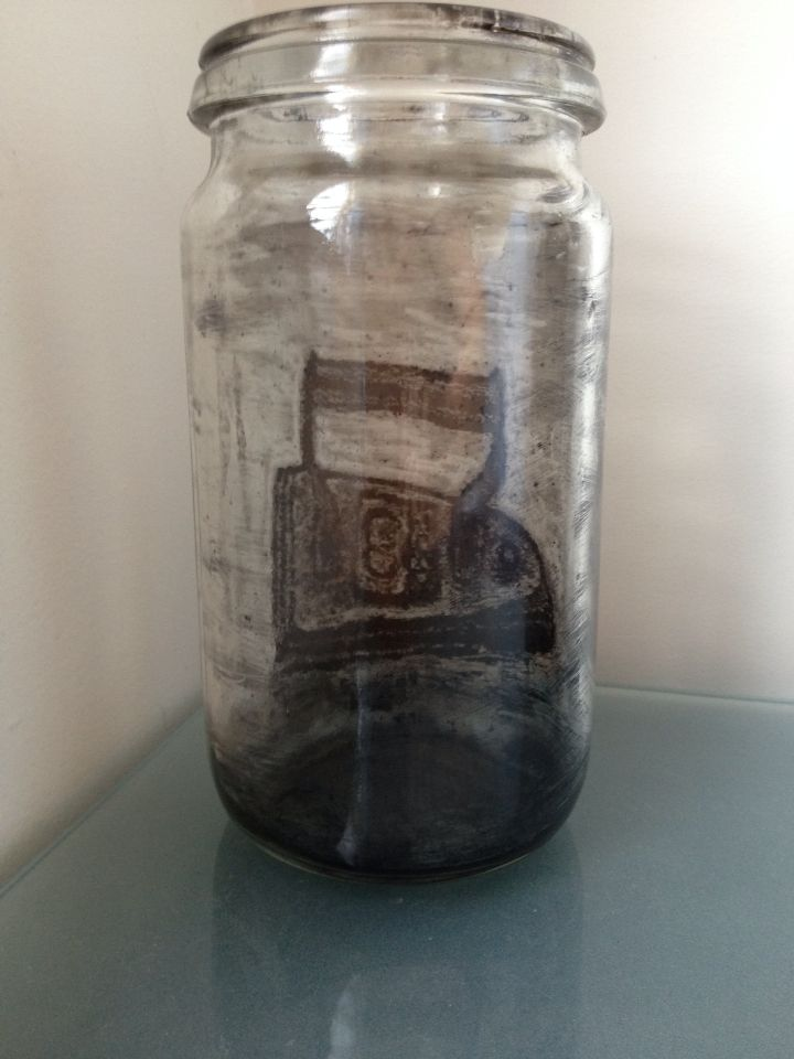 An old iron, drawn in soot inside a preserving jar.