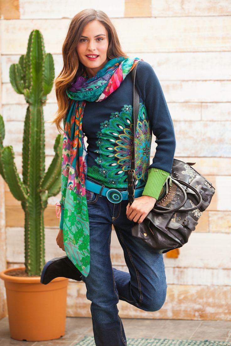 Camiseta de mujer Desigual modelo Danae. El estampado tiene brillantes incrustados y unos acabados de purpurina súper chulos. Puños de canalé con lazo de terciopelo.