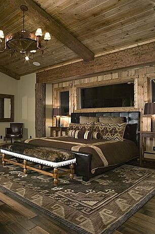Rustic wood paneled master bedroom with black leather bed and neutral western bedding.