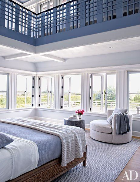 In the master bedroom, a Room & Board swivel chair is positioned to take in the view; the bed is draped with a Calvin Klein Home blanket, and the rug is by Stark.