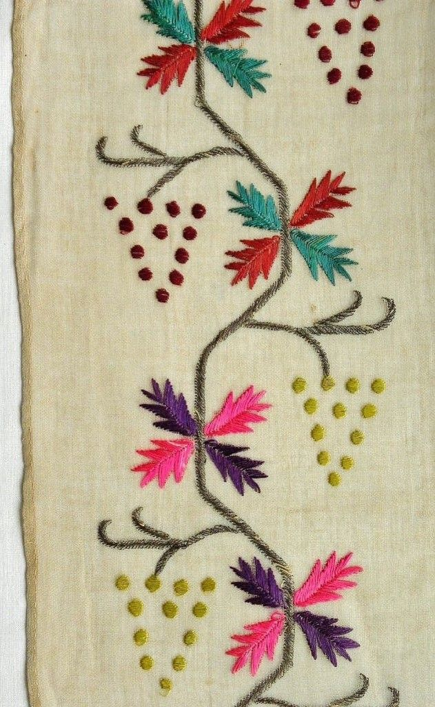 A detail of a large embroidered headscarf, Crimean Tatar, probably from Romania, c. early 20th century.  Called 'marama'.  Embroidered on cotton (muslin), 75 x 139 cm. Featuring red & green grapes, + grape leaves on a meandering stem (flowing water motif), worked with metallic thread (silver), all in satin stitch.  Height of embroidery (from the tip of silver stems to the edge of cloth): 14 cm. Note the absence of a border.  (The Asiye-Zeynep Collection, Washington DC).
