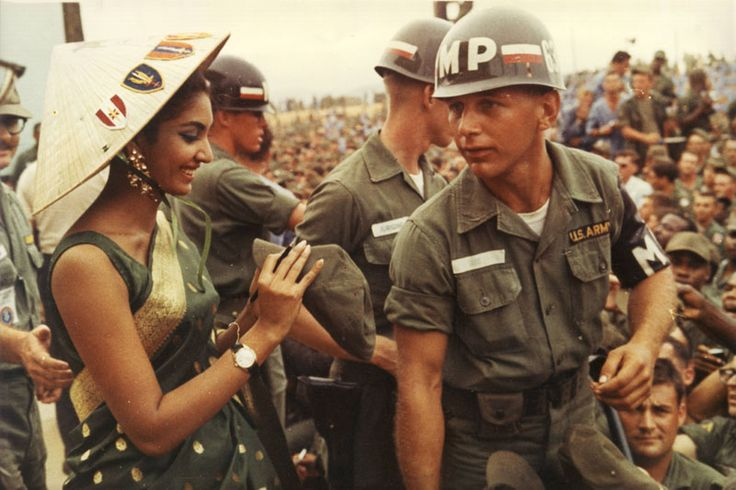 The first Indian Miss World, Reita Faria, signing a cap for US troops in South Vietnam, 1966