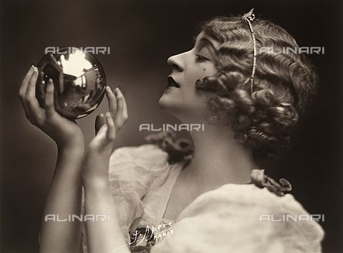 Close-up of a young woman looking at her reflection in a metallic sphere. (c)Fratelli Alinari Museum Collections-Favrod Collection, Florence