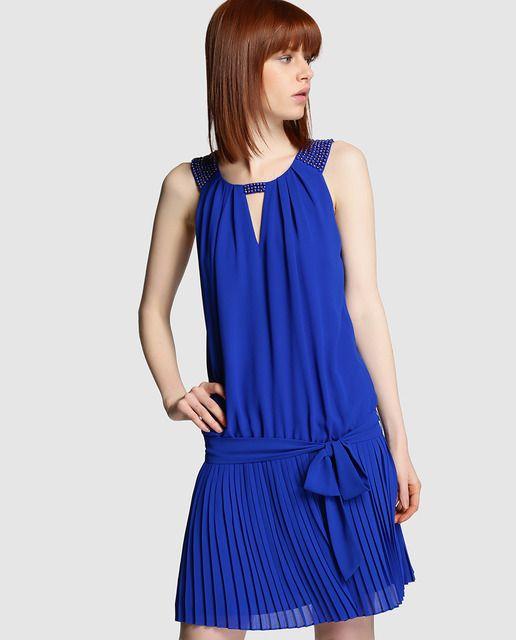 Vestido corto en color azul, con falda plisada y adorno de strass. Sin mangas, con lazo en la cintura y escote redondo.