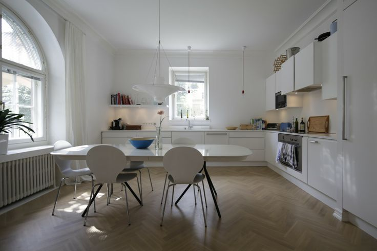 A Scandinavian white open space kitchen. Wooden floors. Finnish design Lokki lamp. Oval white table.