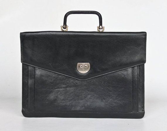 A nice business folio briefcase made from a genuine thick black leather probably sometime in the 1980s. Inner space is divided on four open
