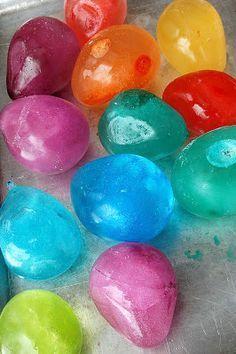 Gelo colorido em forma de pedra: bexigas cheias de agua colorida com anilina. Colocar no freezer e depois de congelado, quebrar balao! Lindos pra brincar e para decoraçao festa!