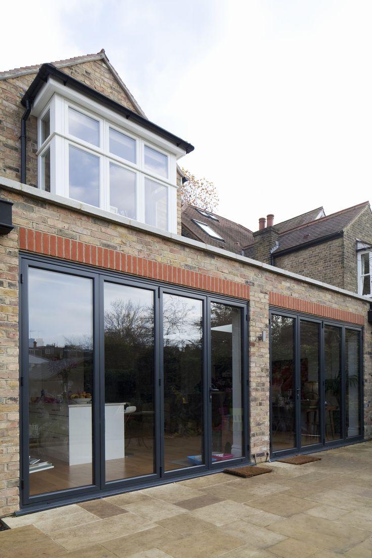 Rear extension   brick   flat roof   hidden drainage   parapet upstand   grey alumuminium bi-fold doors   patio   stone coping
