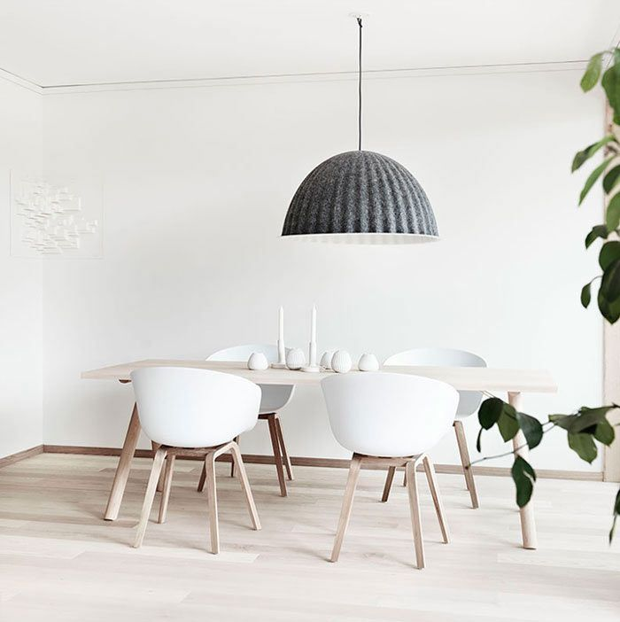 Designed and styled by Folkhem, this minimalist dining room in Sweden is covered in white and light wood tones, complete with an oversized, ribbed grey felt Under The Bell Pendant from Muuto.