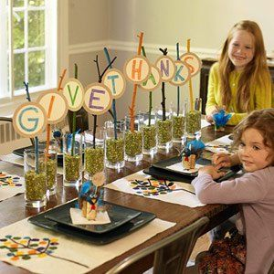 Let your kids help you make the centerpiece for their table. All you need is some twigs, paint, lentils, letters and glass jars! They'll love looking at their hard work during dinner. Find more Thanksgiving recipes and crafts at http://cakemate.com.