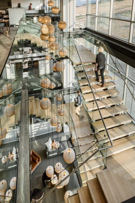 A staircase with wooden treads and glass railings zigzags up through this atrium and sculpted cardboard globes affixed to thin cables are suspended from the ceiling.