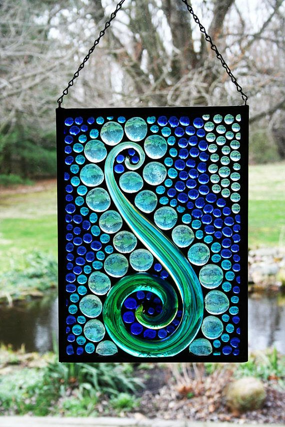 This stained glass panel usues a found object, an Italian blown glass item that I found in the clearance department of a local store. I loved the change in blues and greens in the glass, so I surrouned it with cobalt and mediterranean turquoise nuggets. It sort of reminds me of an abstract G-clef so it seems to elicit a cool jazz musical response from my brain when I look at it. It measures 13 x 10 with hanging eyes and chain. The entire work is done in the tiffany style with copper foil.