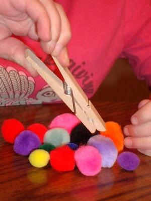 Handen versterken met pompons en knijpers. Gebruik verschillende vingers en de duim om te knijpen. Goede voorbereiding voor het schrijven. Voor nog meer pret, kleur de vingernagels in de kleuren van de pompons en gebruik de 'goede' vinger. Los laten op een gekleurd vlak papier of matje, de pompon mag niet wegrollen. Of de pompons wegschieten met de goede kleur vinger en de duim (vinger in de duim buigen) en mikken tot in een hoepel, op matje of in een doel. Succes verzekerd!
