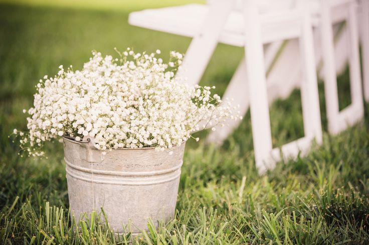 old galvanized buckets overflowing with baby's breath decorate the wedding aisle - thereddirtbride.com - see more of this wedding here