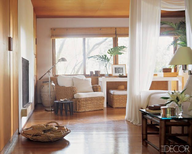 The master bedroom of legendary designer Ralph Lauren's Montauk getaway is a tropical escape, complete with rattan furnishings and breezy curtains that hang from a custom-made teak tester bed. The floor lamp and Scott Madras cotton bed curtains are by Ralph Lauren Home. Tour Ralph Lauren's other home here.
