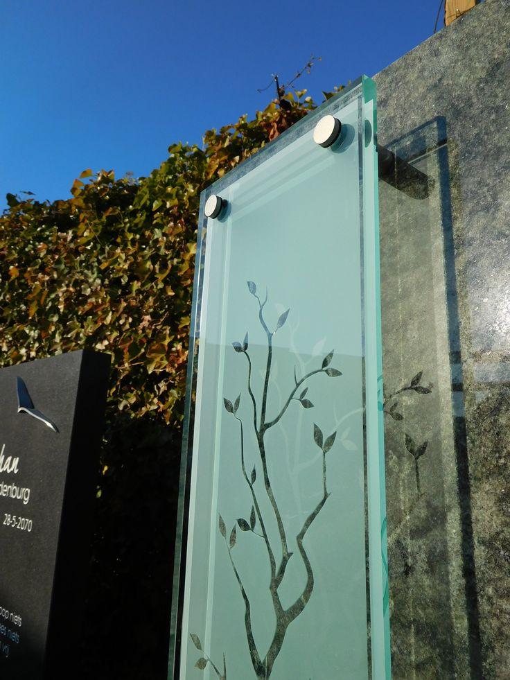 Glas toegepast op een moderne grafsteen. De RVS glashouders doen geen afbreuk aan de uitstraling.