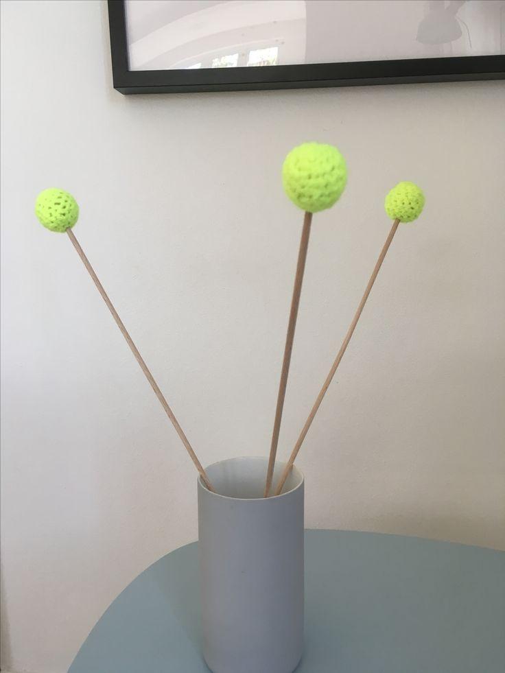 Trommestikker strikket om en træperle i neon gul