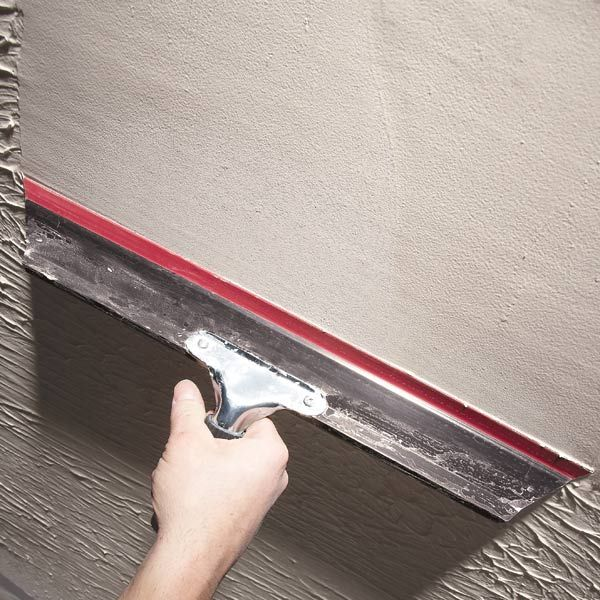 Smooth over rough or damaged walls with a skim coat of mud, applied with a special squeegee knife. It's easy to do and delivers great results.