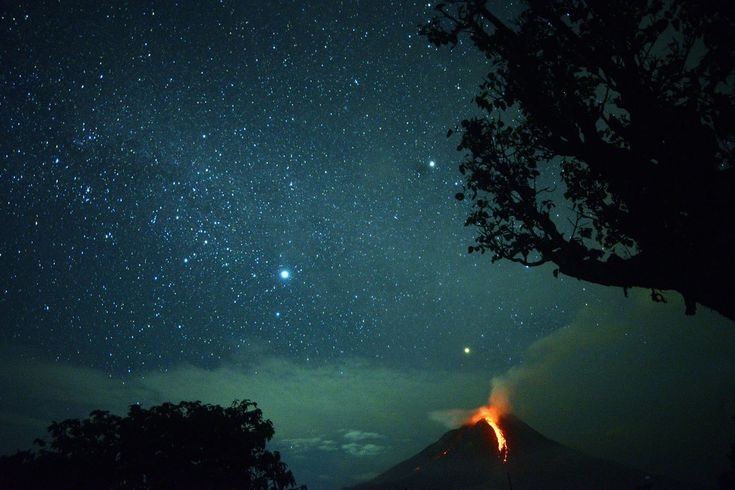 This long-exposure photo taken on December 28, 2017, shows Mount Sinabung volcano spewing lava, as well as the night sky above Karo, North Sumatra.